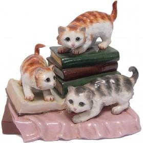 Drie poezen spelend op boeken porseleinen beeldje